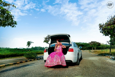 The bride striking a quirky pose, while sitting in the dickey of her car.