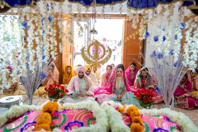 The couple and their families immersed in prayer during the Anand Karaj ceremony.