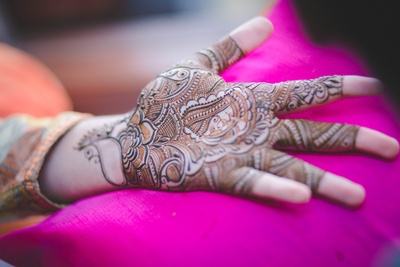 Hands covered in intricately patterned with bridal Indian mehndi design