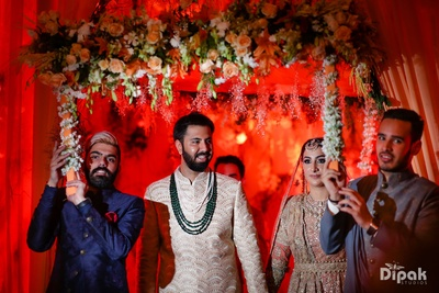 bride and groom entering the wedding ceremony under the floral chadar