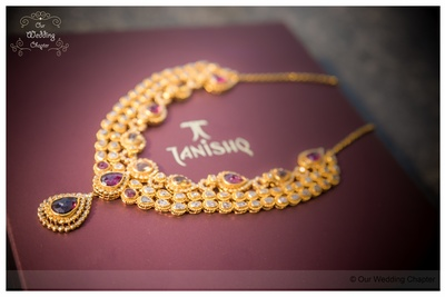 Gold necklace set studded with kundan and gemstones with a matching pendant drop