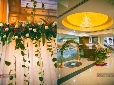 Wedding venue decorated with clustered floral arrangement made with Ferns, red and White Roses and leaves