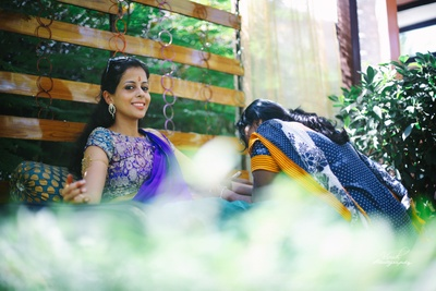 Bride wearing royal blue saree with brocade blouse styled with diamond earrings and a baaju bandh.