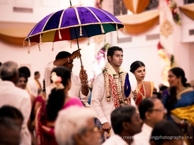 Groom entering the wedding venue in a white shirt and lungi with layers of garlands