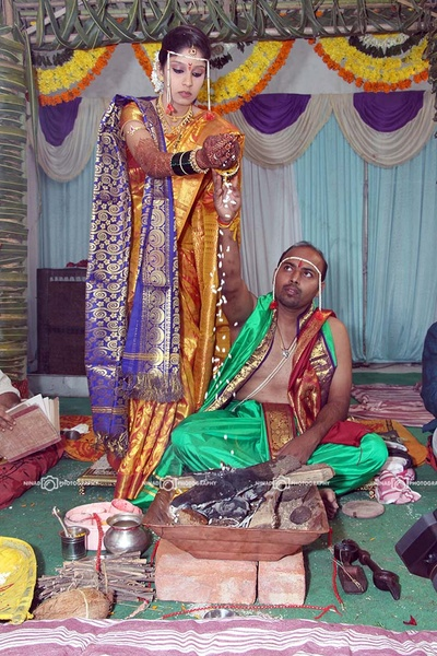 Tree green angavastram and dhoti for the havan. Bride wearing gold silk saree accompained with purple shaalu