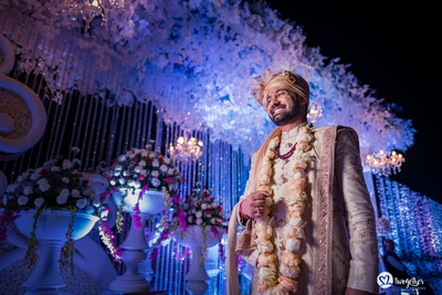 Gorgeous floral wedding decor with the groom in an off white sherwani