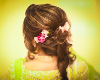 Curled evening half updo adorned with artificial hair accessories