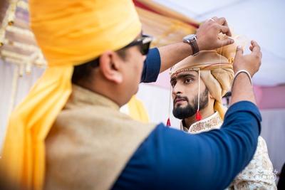 The groom getting his safa tied.