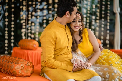 the bride and groom at the haldi ceremony