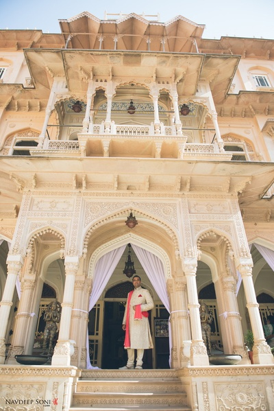 Dressed in an off-white dupatta and orange dupatta for royal destination wedding at Chomu Palace, Jaipur