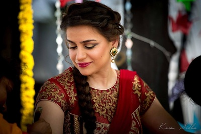 Maroon mehendi outfit styled with radiant bridal makeup