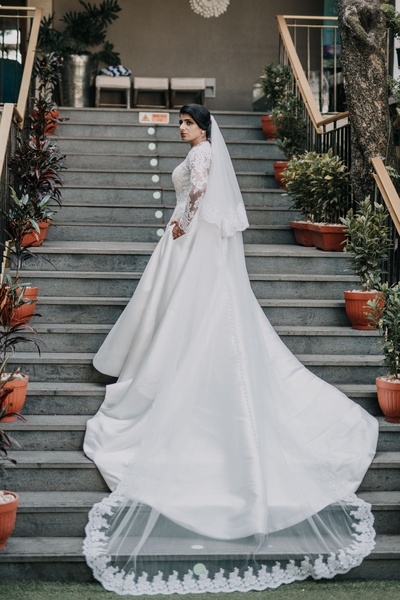 The bride looks stunning in her white wedding dress with a long trail.