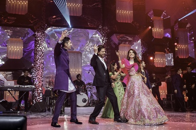 the bride and groom dancing with Shahrukh Khan at the cocktail night