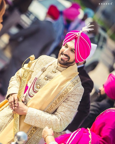 Royal white and gold sherwani paired with beige dupatta and bright pink turban.