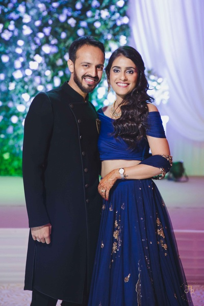 The bride and groom dressed in coordinated navy blue outfits for their sangeet