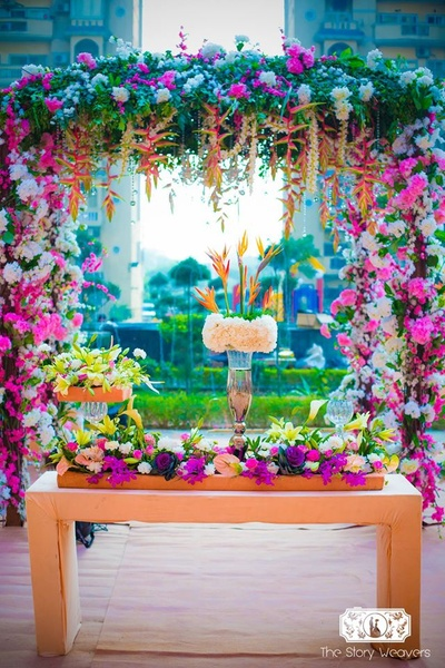 Clustered floral arrangement in a floral gate with fresh flowers in hues of pink, purple and white complimented with fresh green ferns