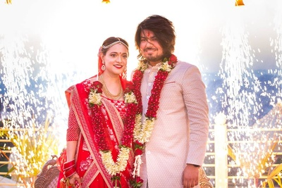 Kriti in red lehenga with minimal bridal jewellery and Rohan in off white bandhgala for their wedding day.