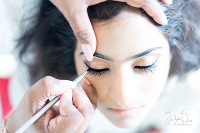 Bride getting her make up done by Sharmistha Thampi for her wedding day.