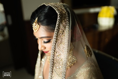 close up of the bride adorned in kundan jewellery and maang tika on the wedding day