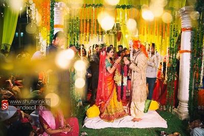 Jaimaala ceremony, groom wearing a beige textured sherwani styled with a silk dhoti