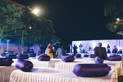 White and mauve themed outdoor evening event with mauve bolsters and white gaddas