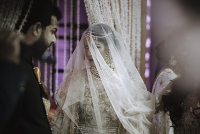 A candid photo of the bride as she walks towards the stage.