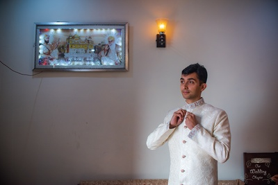 Harsh getting ready in a white sherwani for the wedding.