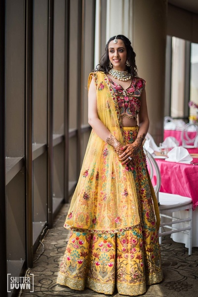 The bride in a pretty emroidered yellow lehenga by Varun Bahl for her mehendi