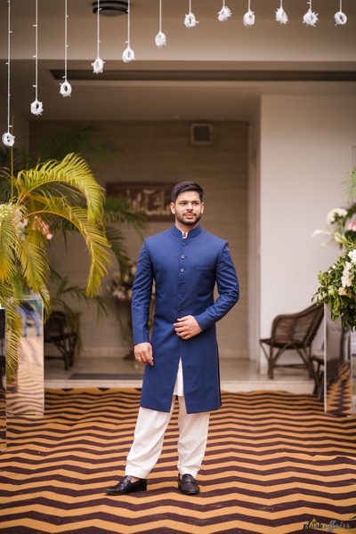 The groom looks dapper in his crisp blue baandhgala paired with white pants.