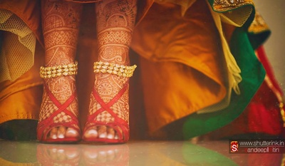 Three-tier gold payal studded with drop shaped jadtar stones, accentuating the bride's mehendi covered feet