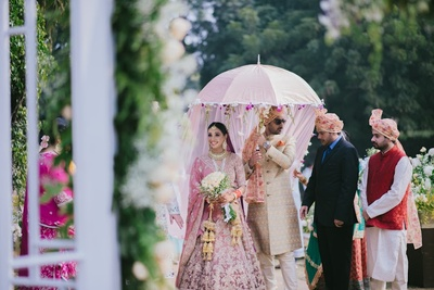 the bride walking down the aisle next to her twin brother under a satin umbrella