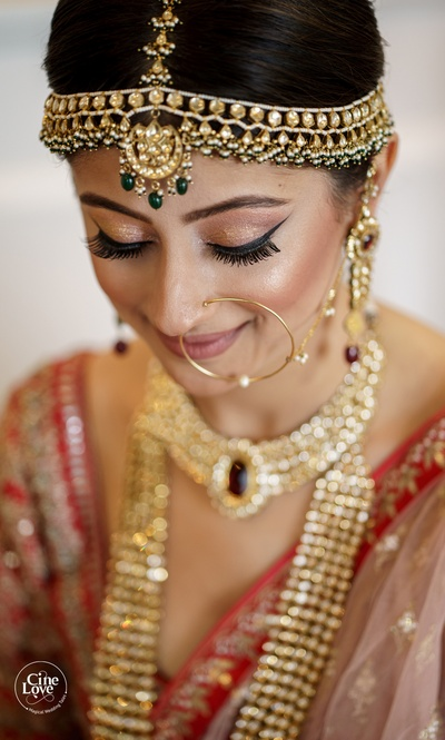 The bride looks nothing less than a royal princess in a traditional red lehenga and kundan jewellery.