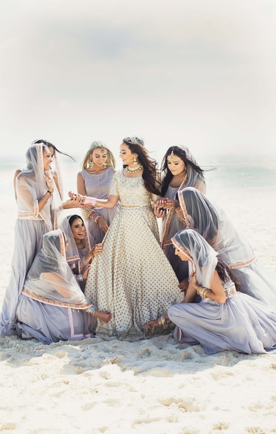 Bride and bridesmaids on the Cancun beach in matching grey lehengas