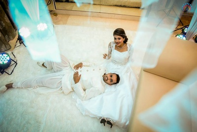 Couple dressed in white attire, matching the decor