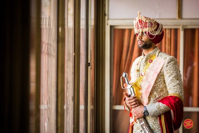 The groom posing in his ivory sherwani