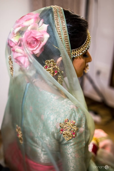 Tanvi shows off her pink rose bun paired with her teal and fuschia bridal lehenga