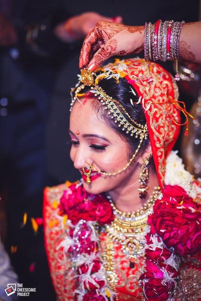 Red wedding lehenga styled with eye shadow and blush on