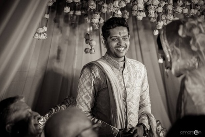 Black and white photography of the groom receiving the bride at the mandap