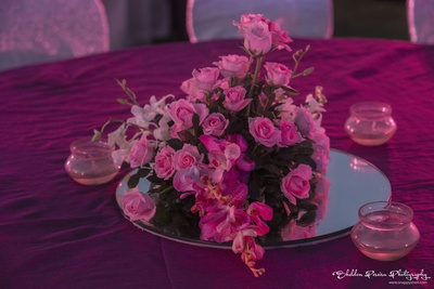 Fresh pink roses on mirror plate as table centrepiece