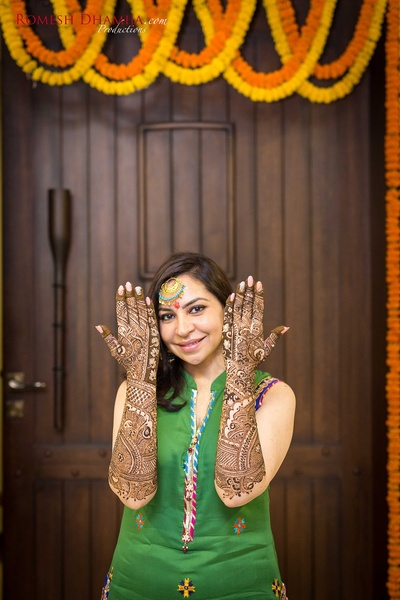 Hands filled with intricate bridal mehendi designs.