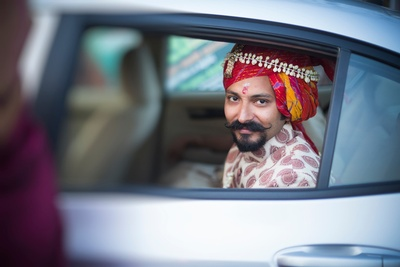 Groom wearing a multi-colored bandhani safa adorned with white Mogra flowers