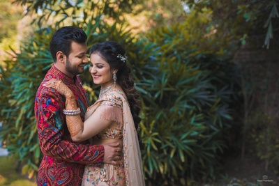 The groom perfectly compliments the gorgeous bride in his vibrant, paisley print bandhgala