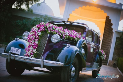 Vintage car decorated with clustered floral arrangement of Orchids and ferns