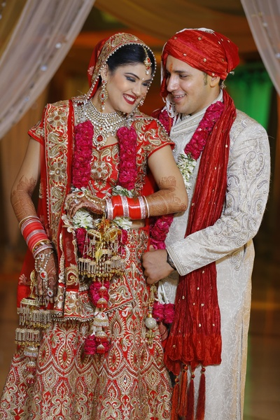 Traditional Red bridal lehenga featuring heavy gold threadwork and sequins