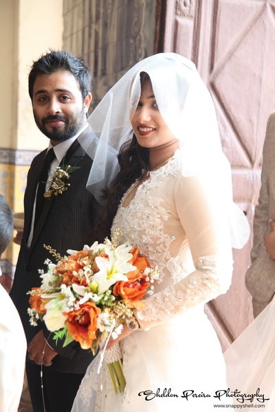 Bride holding a floral bouquet with a netted veil over her face
