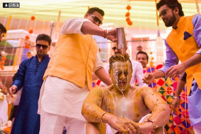 Drenched in yellow, this ecstatic groom goes through his vibrant haldi function