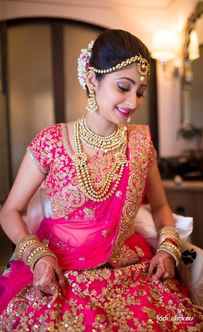 Pink bridal lehenga embellished with gold sequined motifs and polki studded necklace set
