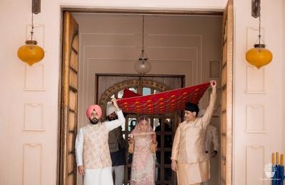 Bride entering the wedding ceremony under a floral chadar
