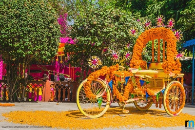 Cycle rickshaw decorated with orange Marigold flowers, paper fans and shimmery garlands