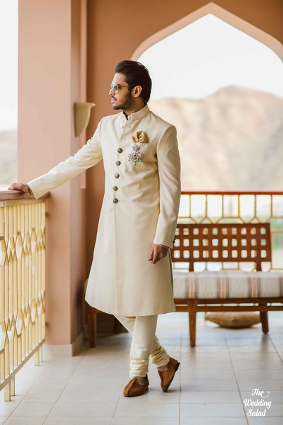 Off-white regal looking achkan with oxidized button detailing, silver brooch and gold pocket square